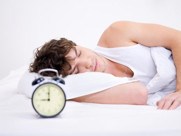 Der junge mann schläft mit wecker in der nähe seines kopfes