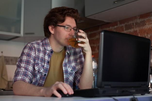 Der junge mann sitzt an einem laptop.