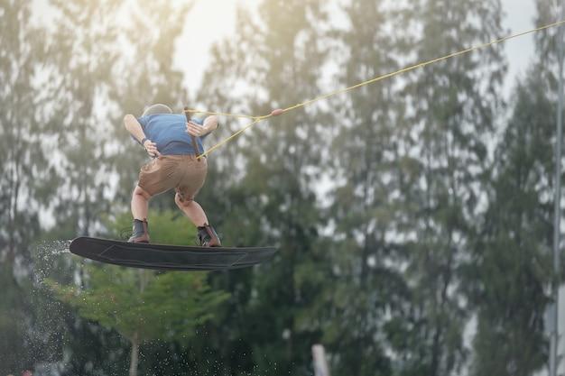 Der junge mann springt beim wakeboarding. extremsport für spaß.