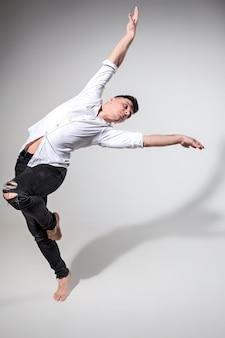 Der junge mann tanzt auf grau