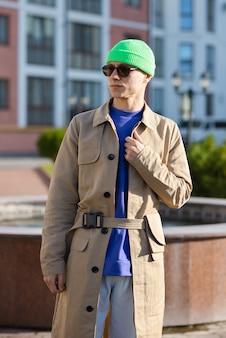 Der junge mann trägt einen modernen mantel, einen grünen hut, weiße jeans und einen pullover