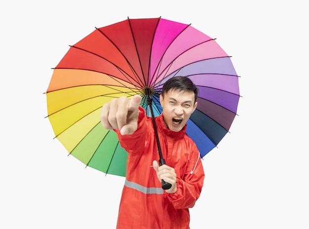 Der junge mann trägt einen roten regenmantel und hält regenbogenfarbe des regenschirmes