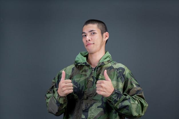 Der junge mann trägt einen tarnregenmantel und zeigt verschiedene gesten.