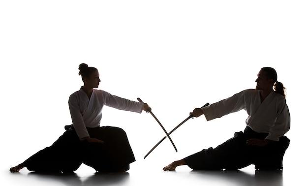 Der junge mann trainiert aikido im studio mit saberaikido-meister übt verteidigung