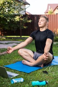 Der junge mann treibt am sommertag zu hause im hinterhof sport. fröhlicher sportler mit blonden haaren meditiert im lotussitz und ruht auf der matte im garten