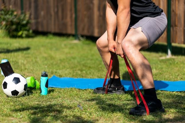 Der junge mann treibt am sommertag zu hause im hinterhof sport. junge sportler machen kniebeugen mit sportgummi auf der matte, es gibt einen laptop, einen ball, dumbeels.