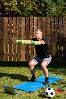 Der junge mann treibt am sommertag zu hause im hinterhof sport. junger sportler mit blonden haaren macht kniebeugen mit hanteln auf der matte, es gibt einen laptop, einen ball und einen gummi für sport in der nähe