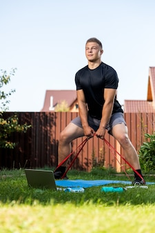 Der junge mann treibt im sommer zu hause im hinterhof sportjunger sportler mit blonden haaren