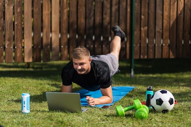 Der junge mann treibt sport im garten. sportler mit blonden haaren trainiert, macht schaukeln und schaut sich einen film an, schaut sich online ein training auf dem rasen an