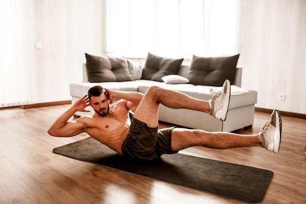 Der junge mann treibt zu hause sport. bild eines sportlers ohne t-shirt, der auf einer yogamatte bauchmuskeln trainiert. workout-neuling, der körper aufwärmt. stretching allein in sonniger wohnung.