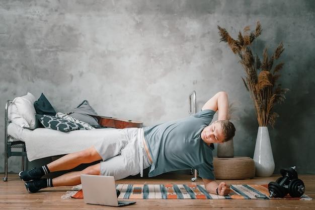Der junge mann treibt zu hause sport und trainiert online. der athlet hält die planke auf der seite, schaut auf einem laptop im schlafzimmer auf die zeit, im hintergrund ein bett, eine vase, einen teppich.
