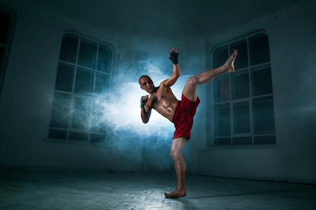 Der junge mann tritt in blauem rauch kickboxen