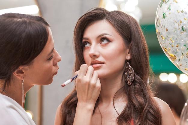Der junge maskenbildner malt die lippen eines schönen mädchens mit einem lippenstift