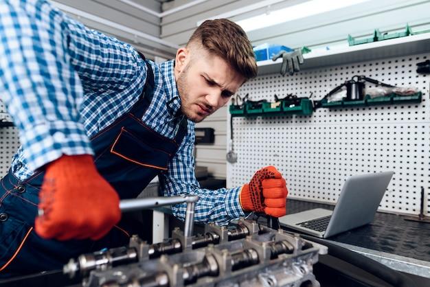 Der junge mechaniker repariert den motor.