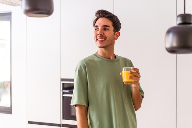 Der junge mischlingsmann, der in seiner küche orangensaft trinkt, sieht beiseite lächelnd, fröhlich und angenehm aus.
