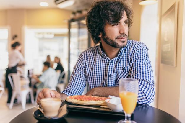 Der junge moderne mann, der am café frühstückt, schaut er durch das fenster