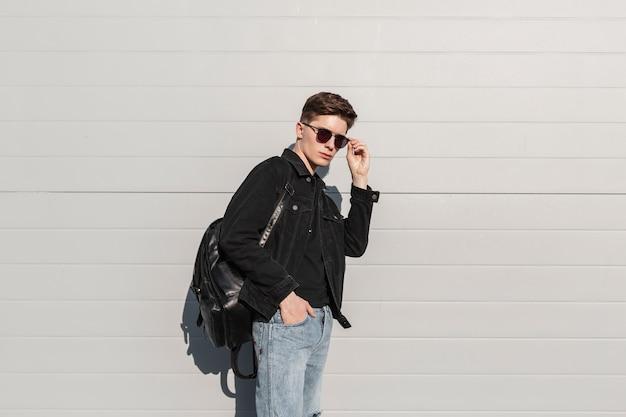 Der junge modische mann richtet an einem sonnigen tag eine stilvolle sonnenbrille in der nähe der vintage-wand auf