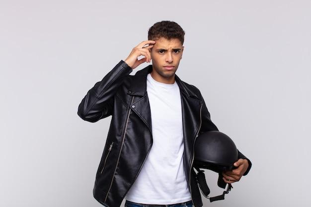 Der junge motorradfahrer fühlt sich verwirrt und verwirrt und zeigt, dass sie verrückt, verrückt oder verrückt sind