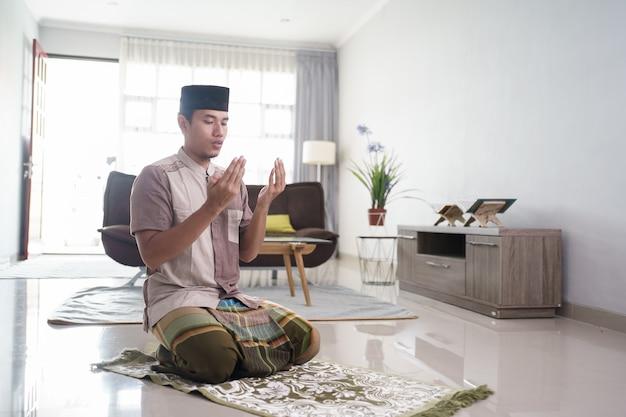 Der junge muslimische mann, der zu hause betet, öffnet seinen arm und bittet gott um vergebung