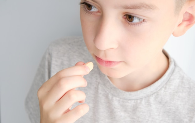 Der junge nimmt die pille in den mund. nahaufnahmen
