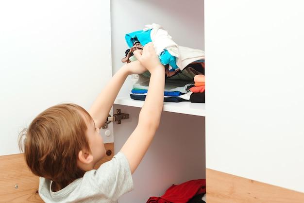 Der junge ordnet die dinge im schrank. kind organisiert kleidung im kleiderschrank. bestellung im schrank.