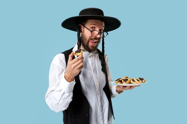 Der junge orthodoxe jüdische mann mit hamantaschen-keksen für das festival purim. feiertag, feier, judentum, gebäck, tradition, keks, religionskonzept
