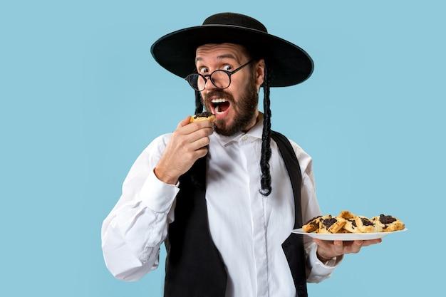 Der junge orthodoxe jüdische mann mit schwarzem hut mit hamantaschen-keksen für das jüdische fest von purim
