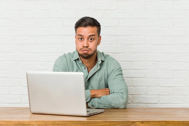 Der junge philippinische mann, der das arbeiten mit seinem laptop sitzt, brennt backen durch, hat müden ausdruck. gesichtsausdruck konzept.