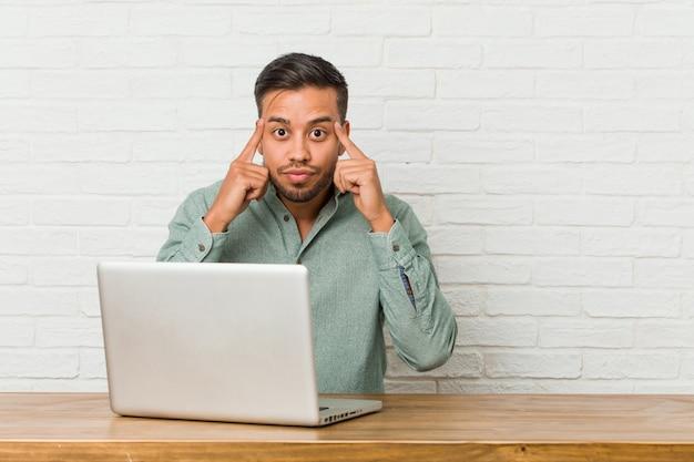 Der junge philippinische mann, der sitzt, arbeitend mit seinem laptop, konzentrierte sich auf eine aufgabe und hielt die zeigefinger, die kopf zeigen.