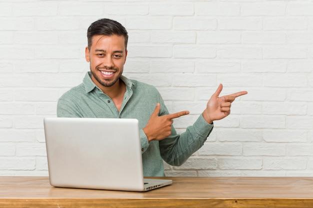 Der junge philippinische mann, der sitzt, arbeitend mit seinem laptop, regte das zeigen mit den zeigefingern weg auf