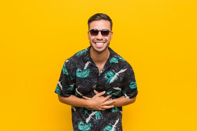 Der junge philippinische mann, der sommerkleidung trägt, lacht glücklich und hat spaß, hände auf magen zu halten.