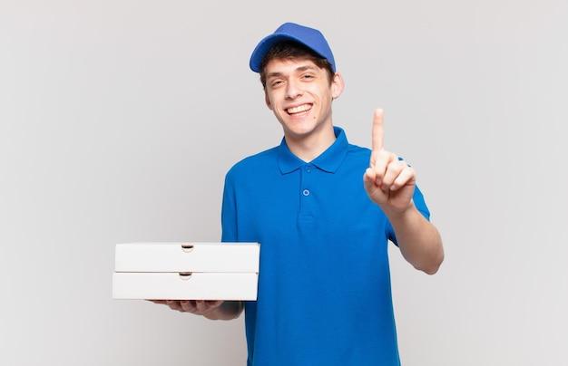 Der junge pizzabote lächelt stolz und selbstbewusst und macht triumphierend die nummer eins und fühlt sich wie ein anführer
