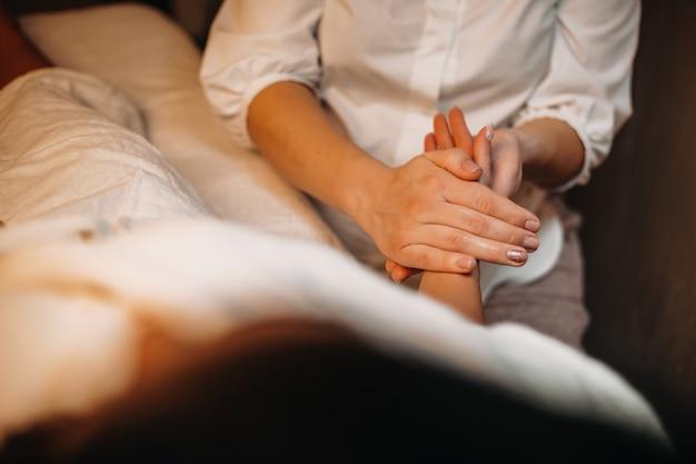 Der junge praktiker hat eine handmassage mit einer frau, die auf dem bett liegt