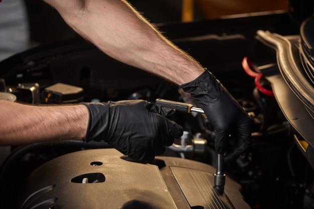 Der junge professionelle automechaniker dreht das fehlende element im auto mit einem schraubenschlüssel