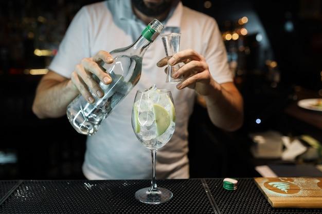 Der junge professionelle barkeeper gießt alkohol aus einer flasche in ein glas in einem nachtclub oder einer bar. köstlichen originellen cocktail kochen. tolles wochenende. nachtleben