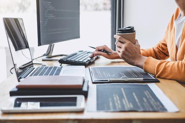 Der junge professionelle programmierer, der an der entwicklung der programmierung und der website in einer software arbeitet, entwickelt das büro der firma, schreibt codes und gibt datencode ein, programmiert mit html, php und javascript