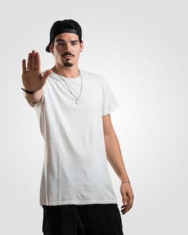 Der junge rappermann, der ernst und entschlossen ist und hand in front einsetzen, stoppen geste, verweigern konzept