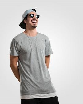 Der junge rappermann, der spaß lacht und hat, entspannt und nett ist, fühlt sich überzeugt und erfolgreich