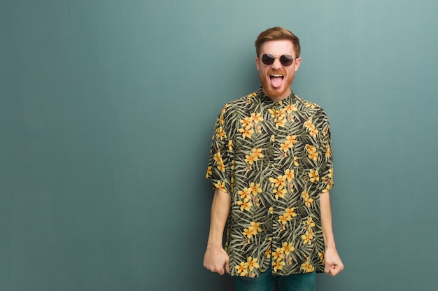 Der junge rothaarigemann, der exotischen sommer trägt, kleidet funnny und freundliche darstellende zunge