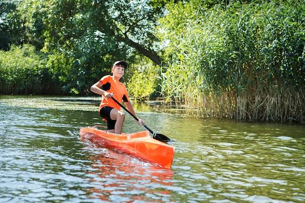 Der junge rudert in einem kanu auf dem fluss. action szenen