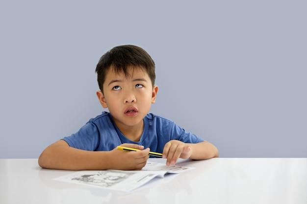 Der junge schaut auf, während er etwas auf dem notizbuch schreibt