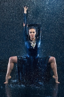 Der junge schöne moderne tänzer, der unter wassertropfen tanzt