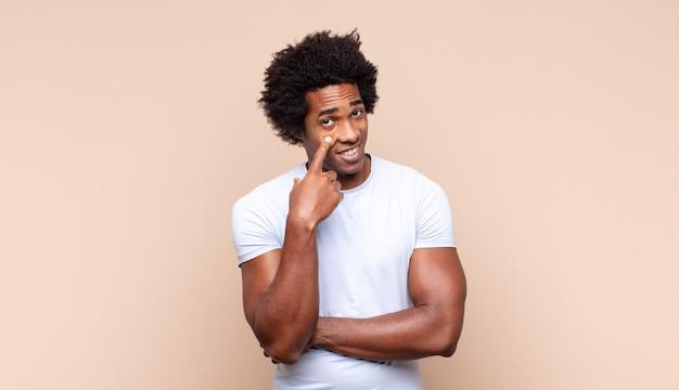 Der junge schwarze afro-mann fühlt sich schockiert, aufgeregt und glücklich, lacht und feiert erfolg und sagt wow!
