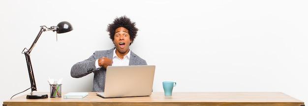 Der junge schwarze geschäftsmann, der entsetzt und mit dem breiten mund überrascht schaut, öffnen sich und zeigen auf selbst auf einem schreibtisch