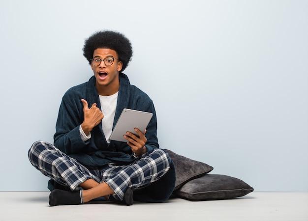 Der junge schwarze mann, der auf seinem haus sitzt und seine tablette überrascht hält, fühlt sich erfolgreich und wohlhabend