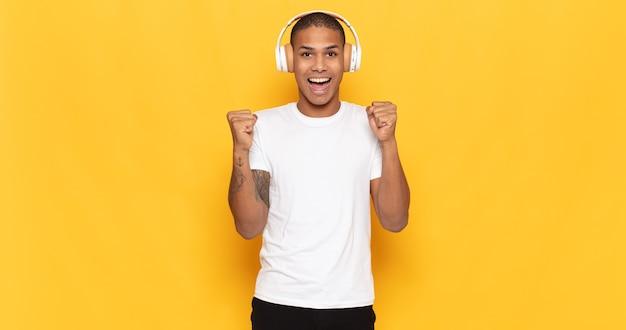Der junge schwarze mann fühlt sich schockiert, aufgeregt und glücklich, lacht und feiert erfolg und sagt wow!