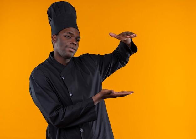 Der junge selbstbewusste afroamerikanische koch in der kochuniform gibt vor, etwas isoliert auf orangefarbenem hintergrund mit kopienraum zu halten