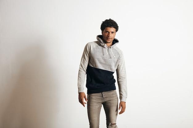 Der junge sexy athlet trägt einen leeren grauen schwarzen kapuzenpullover und verzweifelte jeans, die auf weiß isoliert werden