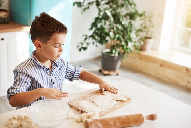 Der junge sitzt am küchentisch gegenüber dem fenster und rollt den teig aus
