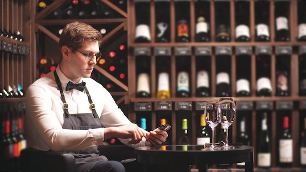 Der junge sommelier macht sich auf seinem smartphone notizen, um in einer weinboutique zu arbeiten